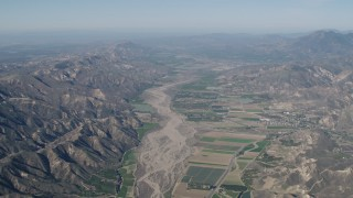 AX70_183 - 4K stock footage aerial video Farm fields and Santa Clara River bordered by mountains in Piru, California