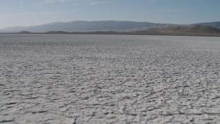 AX70_217 - 4K stock footage aerial video Fly low over Soda Lake in California, to approach desert mountains