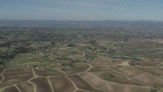 AX70_224 - Aerial stock footage of 4K Aerial Video Passing rural homes, vineyards, and a pond in Paso Robles, California