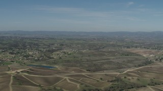 AX70_225 - Aerial stock footage of 4K Aerial Video Flyby rural homes, vineyards, and a pond in Paso Robles, California