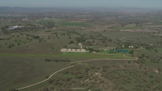 AX70_228 - Aerial stock footage of 4K Aerial Video small airfield beside an upscale home in Paso Robles, California