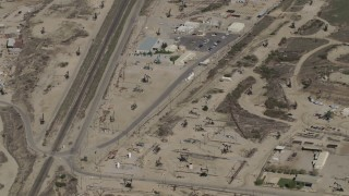 AX70_237 - 4K stock footage aerial video Bird's eye of working oil rigs beside railroad tracks in San Ardo, California