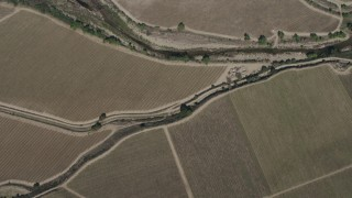 AX70_248 - 4K stock footage aerial video bird's eye view of a river by crop fields, reveal Arroyo Seco Road in Greenfield, California