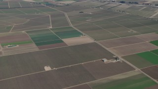 AX70_250 - Aerial stock footage of 4K Aerial Video Vineyards and fields around the Monterey Pacific winery in Soledad, California