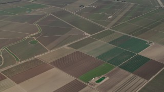 AX70_252 - Aerial stock footage of 4K Aerial Video Flyby crop fields by the intersection of Clark and Arroyo Seco Road in Soledad, California