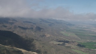 AX70_263 - Aerial stock footage of Fly over Santa Lucia Range mountain slopes and farmland in Soledad, California