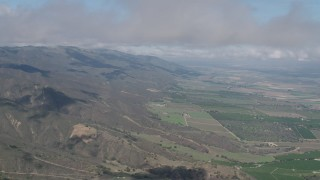 AX70_264 - Aerial stock footage of Cloud-capped Santa Lucia Range mountain slopes and farmland in Soledad, California
