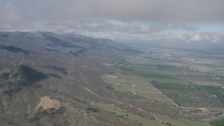 AX70_265 - Aerial stock footage of Flying over Santa Lucia Range mountain slopes beside farmland in Soledad, California