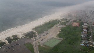 AX71_024 - 5K stock footage aerial video of low fog over Lido Beach condo complexes and homes, Long Island, New York