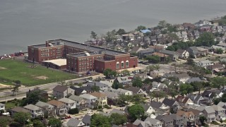 AX71_026 - 5K stock footage aerial video of Lindell Elementary School beside Reynold's Channel in Long Beach, Long Island, New York