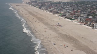 AX71_037 - 5K stock footage aerial video flying over beach goers in Neponsit, Queens, New York