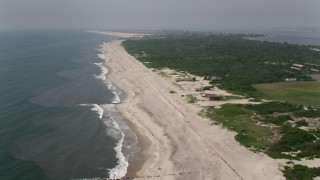 AX71_039 - 5K stock footage aerial video flying over beachgoers and beachfront homes in Fort Tilden, Queens, New York