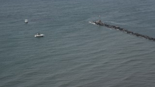 AX71_043 - 5K stock footage aerial video of fishing boats by end of a breakwater in Breezy Point, Queens, New York