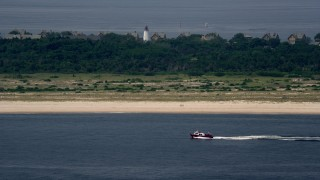 AX71_047 - 5K stock footage aerial video of a fishing boat passing the beach near Sandy Hook Lighthouse, Middletown, New Jersey
