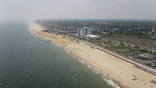 AX71_058 - 5K stock footage aerial video flying by beach goers near Pier Village condo complex, shops, and restaurants in Long Branch, Jersey Shore, New Jersey