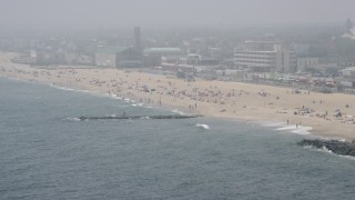 AX71_064 - 5K stock footage aerial video of beach goers on a foggy day in Asbury Park, Jersey Shore, New Jersey