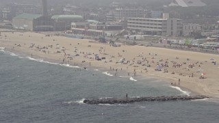 AX71_064E - 5K stock footage aerial video of beach goers on a foggy day in Asbury Park, Jersey Shore, New Jersey
