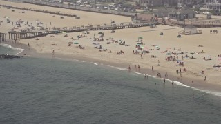 AX71_066 - 5K stock footage aerial video of sunbathers and boardwalk on the beach in Ocean Grove, Jersey Shore, New Jersey