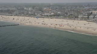 AX71_068 - 5K stock footage aerial video of beach goers and beachfront homes on a hazy day in Avon by the Sea, Jersey Shore, New Jersey
