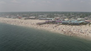 AX71_080 - 5K stock footage aerial video of a crowd of sunbathers around Jenkinson's Boardwalk & Martell's Tiki Bar, Jersey Shore, New Jersey