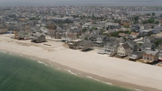 AX71_089 - 5K stock footage aerial video beachfront homes and a people on the beach in Normandy Beach, Jersey Shore, New Jersey
