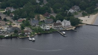 AX71_107 - 5K stock footage aerial video flying by riverfront homes with docks in Pine Beach, New Jersey