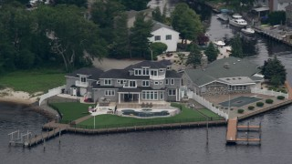 AX71_109 - 5K stock footage aerial video of an upscale riverfront home with a dock in Toms River, New Jersey