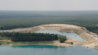 AX71_120 - 5K stock footage aerial video of a quarry lake in Forked River, New Jersey, surrounded by Pine Barrens