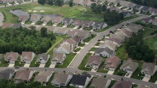 AX71_128 - 5K stock footage aerial video of a suburban neighborhood on a golf course in Waretown, New Jersey