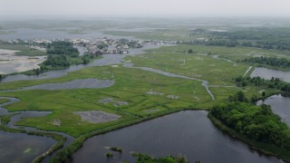 AX71_131 - 5K stock footage aerial video flying over marshland near waterfront homes by canals in Barnegat Township, New Jersey