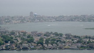 AX71_160 - 5K stock footage aerial video of boats on a bay by coastal neighborhoods in Brigantine, New Jersey