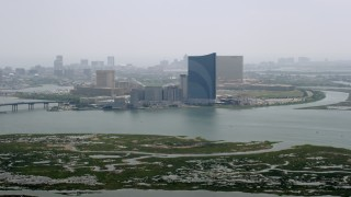 AX71_163 - 5K stock footage aerial video flying over marsh to approach Harrah's Resort Atlantic City, New Jersey