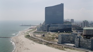 AX71_178 - 5K stock footage aerial video flying by beachfront apartment building and Revel Casino Hotel near Steel Pier, Atlantic City, New Jersey