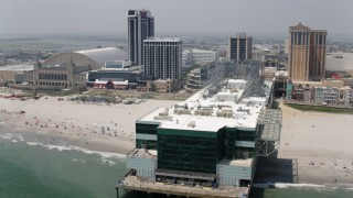 AX71_185 - 5K stock footage aerial video flying by Playground Pier between Trump Plaza and Caesars Atlantic City, New Jersey
