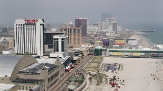 AX71_186 - 5K stock footage aerial video following boardwalk past Boardwalk Hall, Trump Plaza Hotel, toward Caesar's Atlantic City and Playground Pier, New Jersey