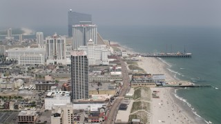 AX71_188 - 5K stock footage aerial video flying over boardwalk past hotels in Atlantic City toward Steel Pier, New Jersey