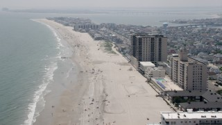 AX71_211 - 5K stock footage aerial video of beach goers and beachfront condo complexes in Margate City, New Jersey