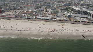 AX71_222 - 5K stock footage aerial video of sunbathers on the beach by Playland's Castaway Cove, Ocean City, New Jersey