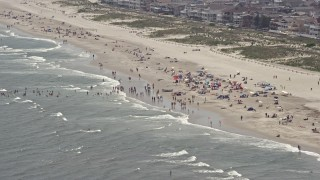 AX71_227 - 5K stock footage aerial video of a crowded beach in Ocean City, New Jersey