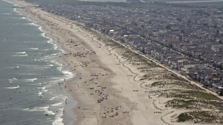 AX71_228E - 5K stock footage aerial video of a populated beach and beachfront neighborhoods in Ocean City, New Jersey