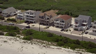 AX71_238E - 5K stock footage aerial video flying by beachside homes in Strathmere, New Jersey