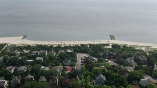 AX72_012 - 5K stock footage aerial video flying over beachfront homes and beach goers in Cape May, New Jersey