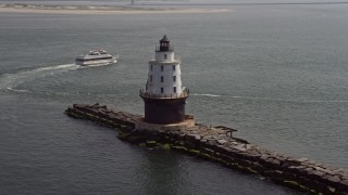 AX72_025 - 5K stock footage aerial video orbiting Harbor of Refuge Light, Delaware and reveal a passing ferry
