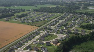 AX72_063 - 5K stock footage aerial video of tract homes by farm field in Magnolia, Delaware