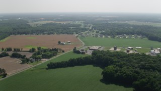 AX72_085 - 5K stock footage aerial video of farms, fields and rural homes by a country road in Dover, Delaware