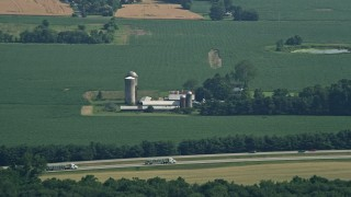 AX72_112 - 5K stock footage aerial video of a farm with silos and barns near the highway in Centreville, Maryland