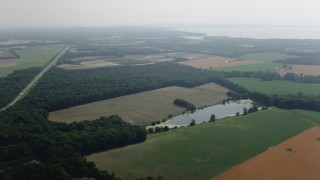 AX72_115 - 5K stock footage aerial video flying over farm fields to approach Reed Creek in Queenstown, Maryland