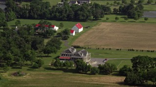 AX72_127 - 5K stock footage aerial video of a large farmhouse, fields, and barns in Stevensville, Maryland