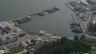 AX73_028 - 5K stock footage aerial video orbiting Navy ships docked in a small harbor in Annapolis, Maryland