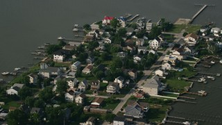 AX73_043 - 5K stock footage aerial video of waterfront houses and boats at a small marina in Hawk Cove at Sparrows Point, Maryland